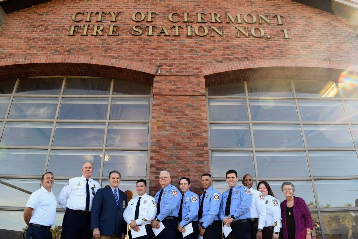 From left, Darren Gray, Carle Bishop, Jimmy Patronis, the seven firefighters and Gail Ash stand in front of the fire station for a photo. This photo is shot at an upward angle to show the City of Clermont Fire Station #1 lettering on the building.