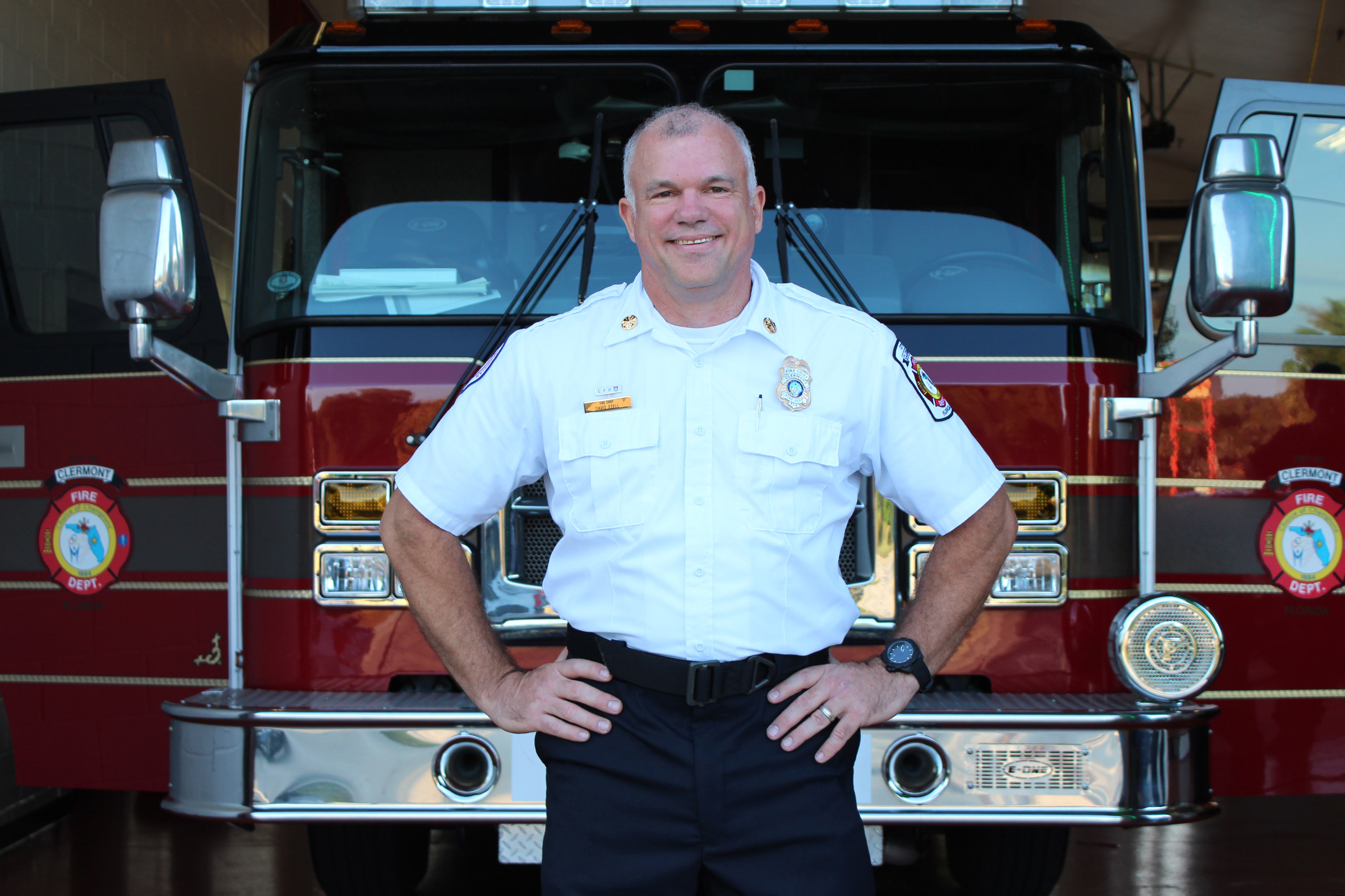 Photo of Chief Ezell standing in front of fire truck smiling