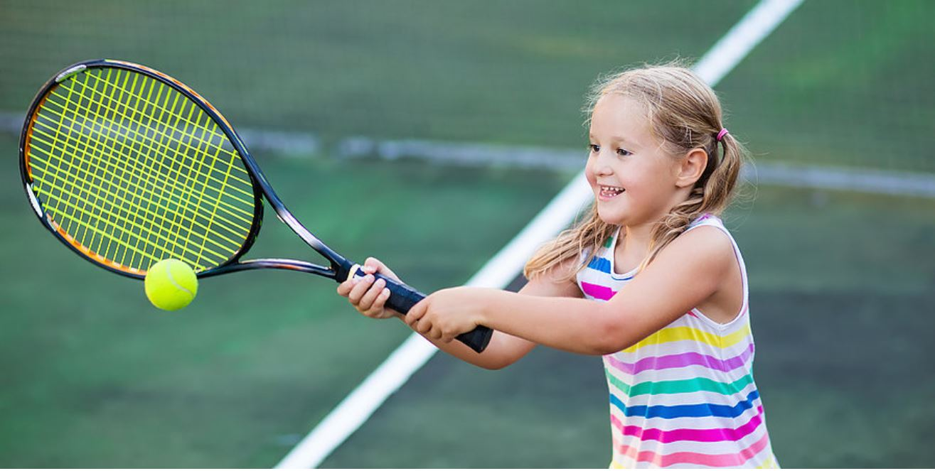 A young girl plays tennis