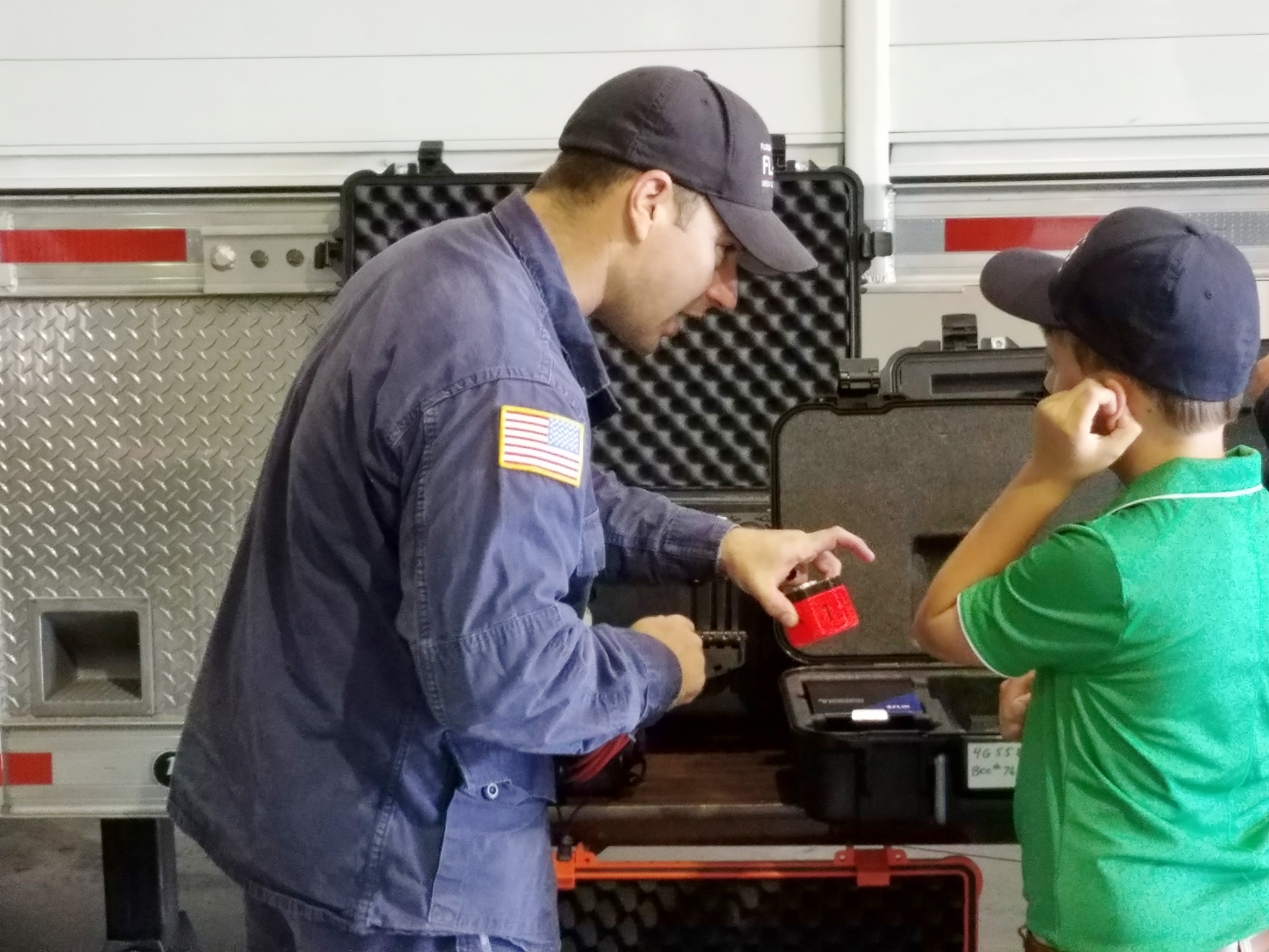 Firefighter speaking with a young boy about the equipment the firefighters use
