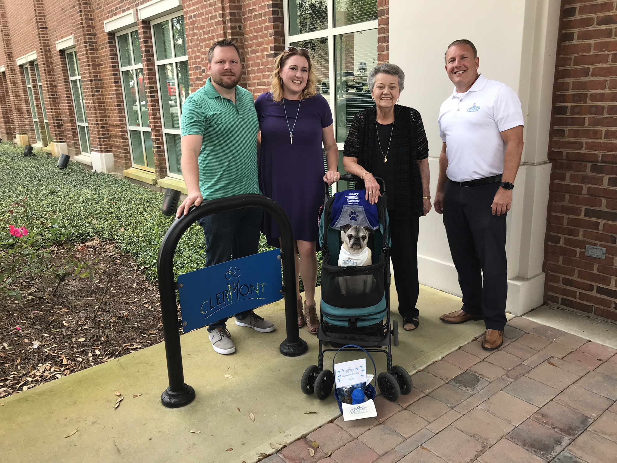 Beefy's owners, left, and Clermont's mayor and city manager stand in front of City Hall with Beefy in the center in his stroller.