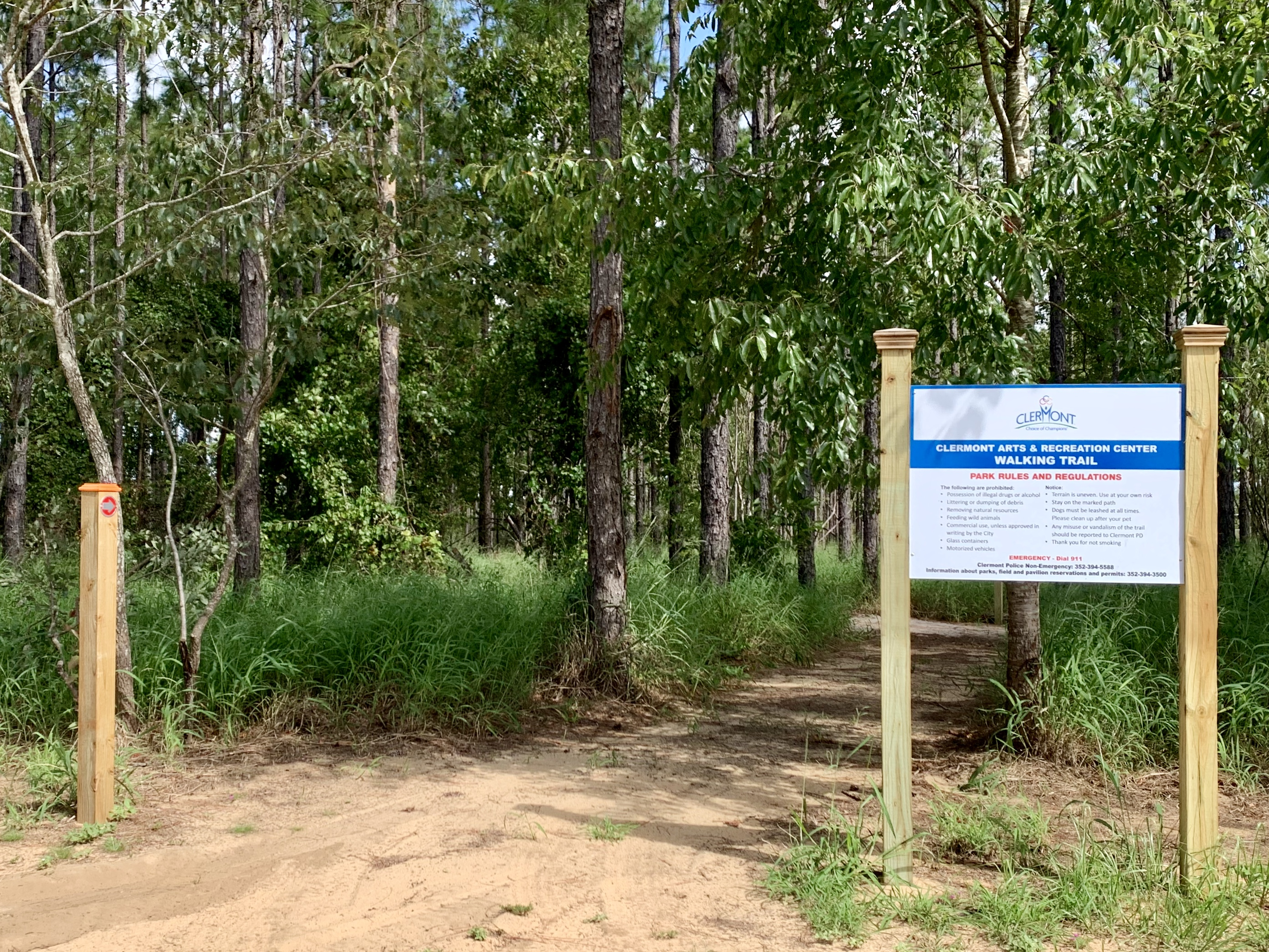 photo of entrance to trail with sign, trees, dirt path, trail post with arrow