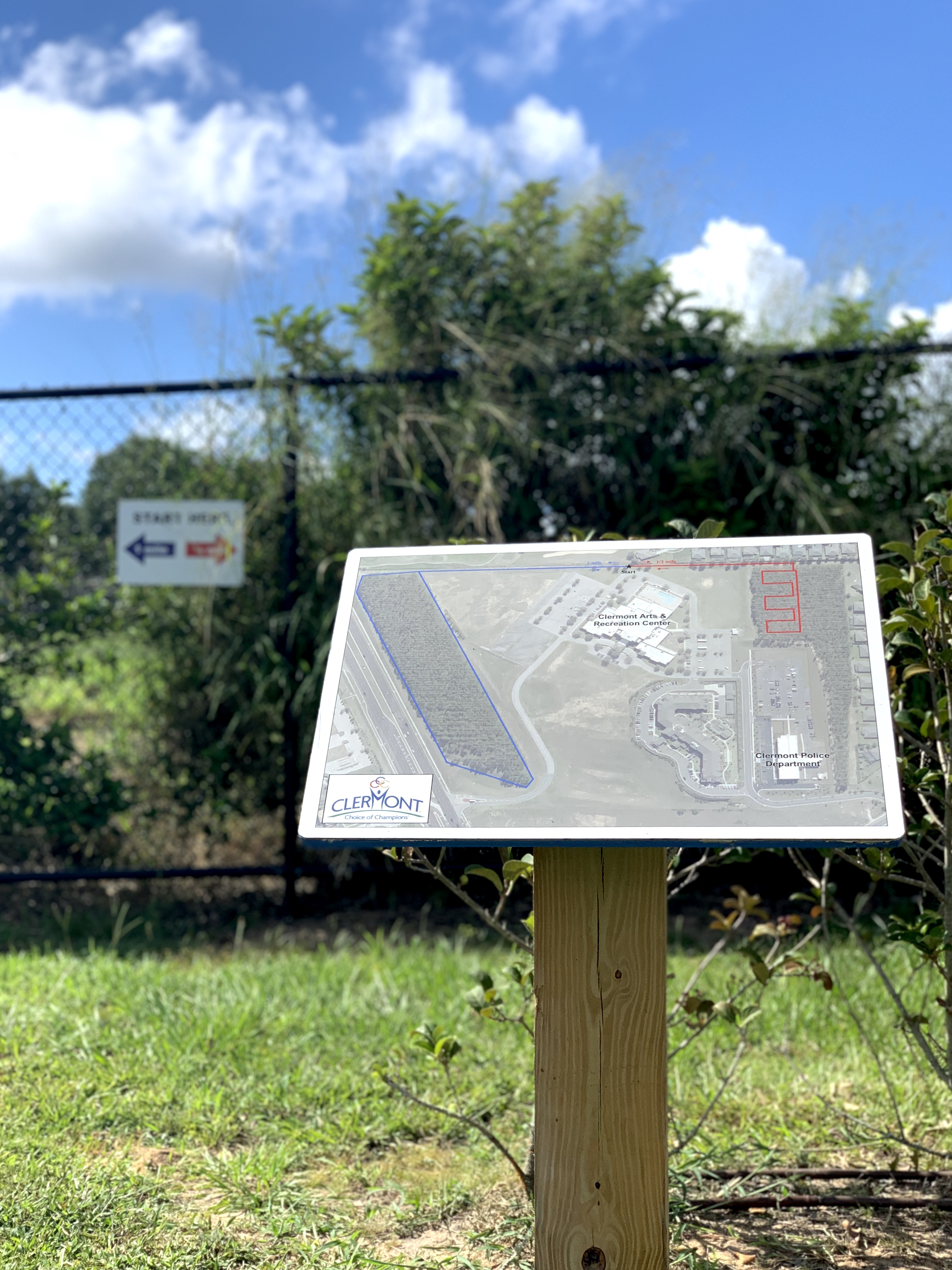 photo showing map displayed on wood stake in grass at trail entrance in front of fence