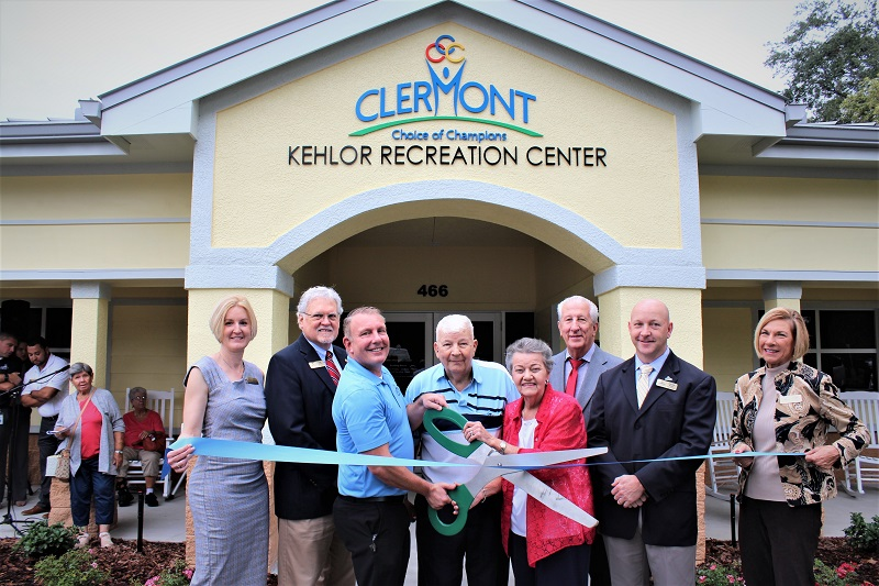 City Manager, Mayor and City Council smile with ribbon and giant scissors in front of new Kehlor Recreation Center